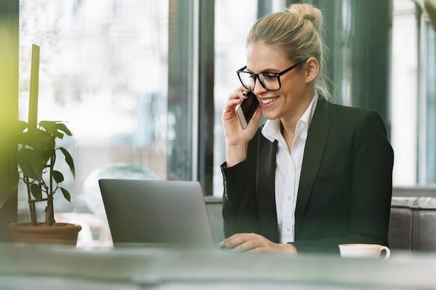 Glimlachende blonde bedrijfsvrouw die door mobiele telefoon spreekt