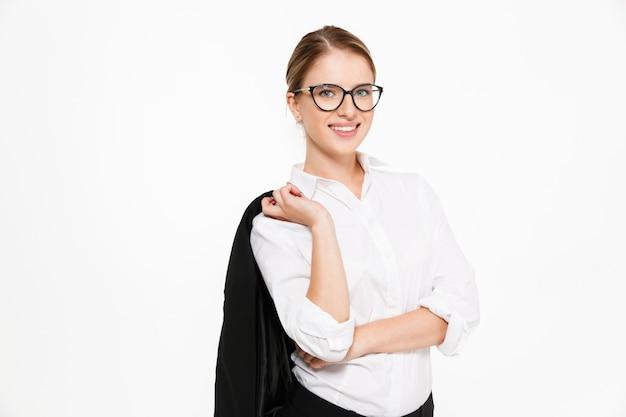 Glimlachende blonde bedrijfsvrouw die in oogglazen haar jasje en over witte muur houdt