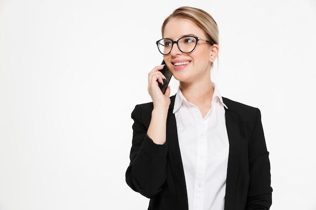 Glimlachende blonde bedrijfsvrouw in oogglazen die door de telefoon spreken en weg over wit kijken