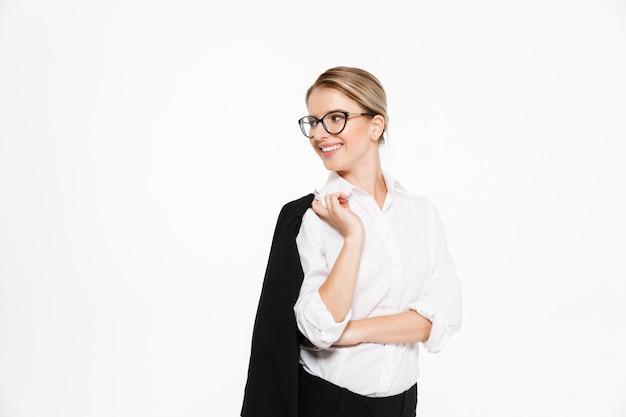 Glimlachende blonde bedrijfsvrouw in oogglazen die haar jasje houden en weg over witte muur kijken