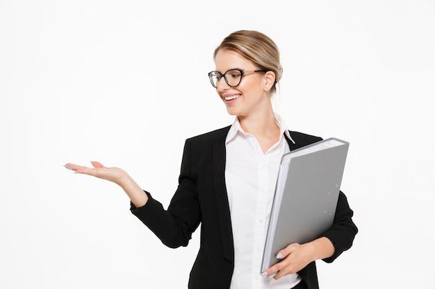 Glimlachende blonde bedrijfsvrouw in oogglazen met omslag in hand holding copyspace op het pond over witte muur