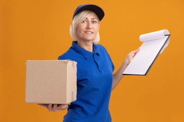 Glimlachende blonde bezorger van middelbare leeftijd in blauw uniform en pet met kartonnen doos en klembord kijkend naar camera geïsoleerd op oranje achtergrond
