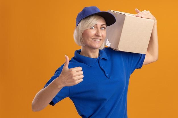 Glimlachende blonde bezorger van middelbare leeftijd in blauw uniform en pet met kartonnen doos op schouder kijkend naar voorkant met duim omhoog geïsoleerd op oranje muur
