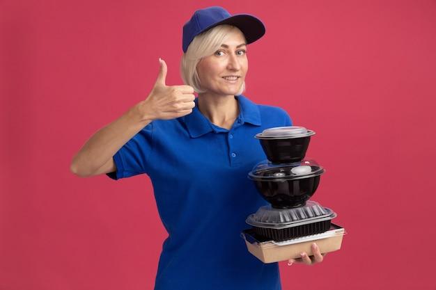 Glimlachende blonde bezorger van middelbare leeftijd in blauw uniform en pet met papieren voedselpakket en voedselcontainers met duim omhoog geïsoleerd op roze muur
