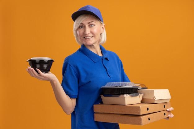 Glimlachende blonde bezorger van middelbare leeftijd in blauw uniform en pet met pizzapakketten met voedselcontainers en papieren voedselpakket erop geïsoleerd op oranje muur