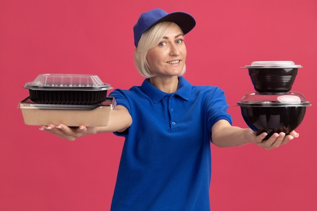 Glimlachende blonde bezorger van middelbare leeftijd in blauw uniform en pet uitrekkend papier voedselpakket en voedselcontainers naar voren kijkend naar voorkant geïsoleerd op roze muur