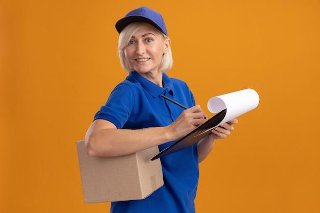 Glimlachende blonde bezorger van middelbare leeftijd in blauw uniform en pet
