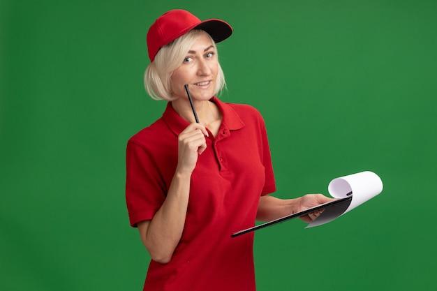 Glimlachende blonde bezorger van middelbare leeftijd in rood uniform en pet die de wang aanraakt met potlood kijkend naar de voorkant met klembord geïsoleerd op groene muur met kopieerruimte