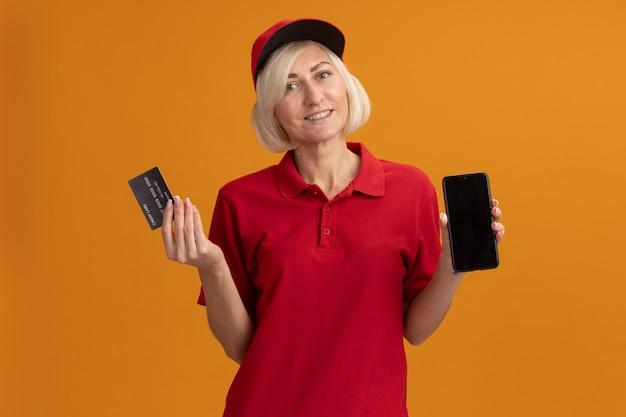 Glimlachende blonde bezorger van middelbare leeftijd in rood uniform en pet kijkend naar de voorkant met creditcard en mobiele telefoon geïsoleerd op een oranje muur