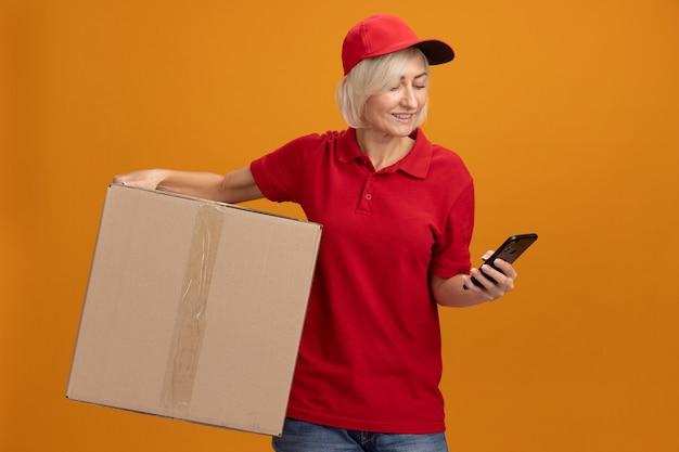 Glimlachende blonde bezorger van middelbare leeftijd in rood uniform en pet met kartonnen doos en mobiele telefoon kijkend naar telefoon geïsoleerd op oranje muur