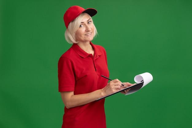 Glimlachende blonde bezorger van middelbare leeftijd in rood uniform en pet staande in profielweergave met potlood en klembord geïsoleerd op groene muur met kopieerruimte