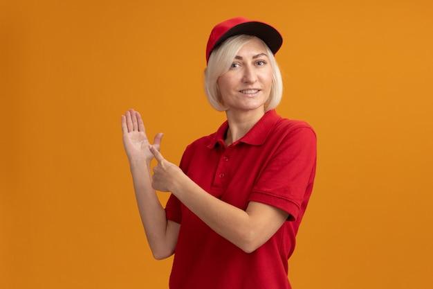 Glimlachende blonde bezorgingsvrouw van middelbare leeftijd in rood uniform en pet staande in profielweergave met lege hand en wijzend naar de hand geïsoleerd op oranje muur met kopieerruimte