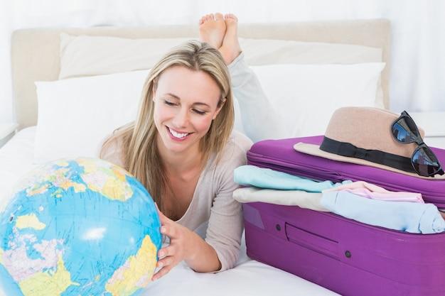 Glimlachende blonde die op bed liggen die haar bol kijken