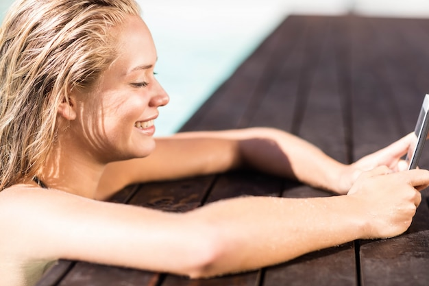 Glimlachende blonde die op poolsrand leunt en smartphone gebruikt