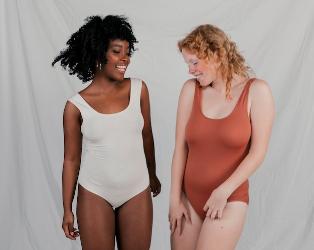 Glimlachende blonde en afrikaanse jonge vrouwen die zich tegen grijze achtergrond bevinden
