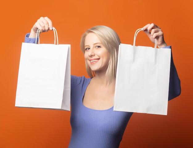 Glimlachende blonde in blauwe blouse met boodschappentassen op een uitbundige oranje kleur achtergrond