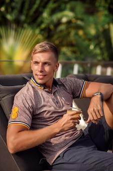 Glimlachende blonde jonge mens in t-shirt die op ligstoelen door zwembad met jus d'orange rusten