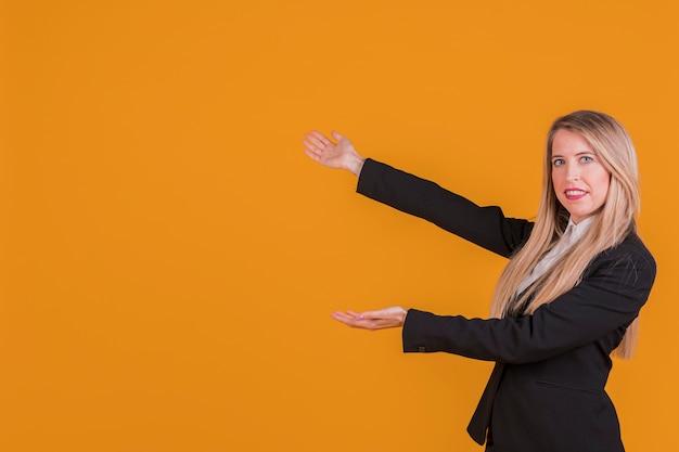 Glimlachende blonde jonge onderneemster die tegen een oranje achtergrond voorstellen