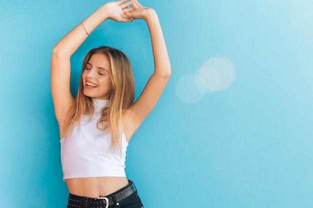Glimlachende blonde jonge vrouw die haar handen opheft tegen blauwe achtergrond