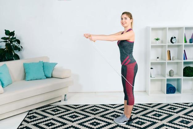 Glimlachende blonde jonge vrouw die met touwtjespringen thuis in de woonkamer uitoefenen