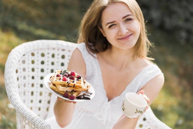 Glimlachende blonde jonge vrouw die plaat van wafels en koffiekop tonen