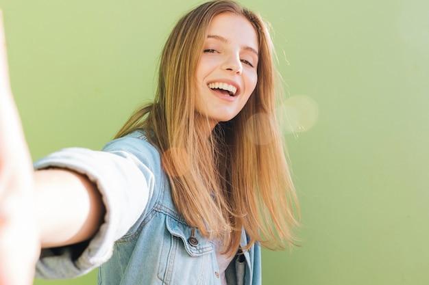 Glimlachende blonde jonge vrouw die selfie tegen munt groene achtergrond nemen