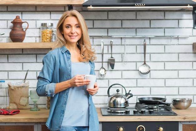 Glimlachende blonde jonge vrouw die zich dichtbij het gasfornuis bevinden die witte koffiekop houden