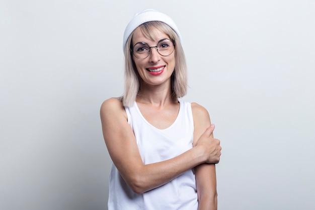 Glimlachende blonde jonge vrouw in glazen, een witte hoed op een lichte achtergrond.