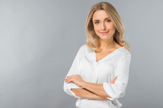 Glimlachende blonde jonge vrouw met haar gekruiste wapens die zich tegen grijze achtergrond bevinden