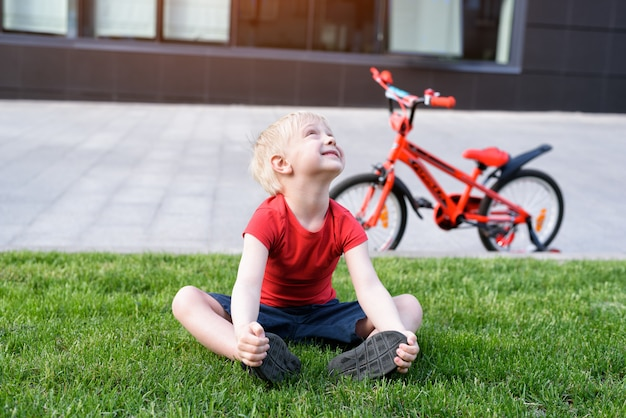 Glimlachende blonde jongen die omhoog zittend op een gazon kijkt