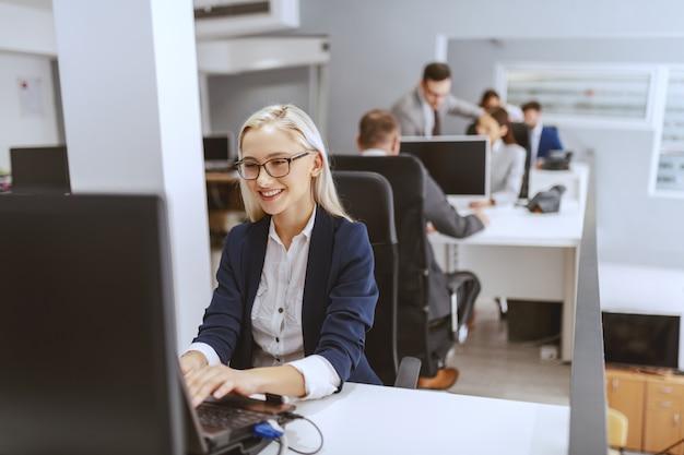 Glimlachende blonde kaukasische onderneemster die op haar werkplaats zit en computer gebruikt. handen op toetsenbord.