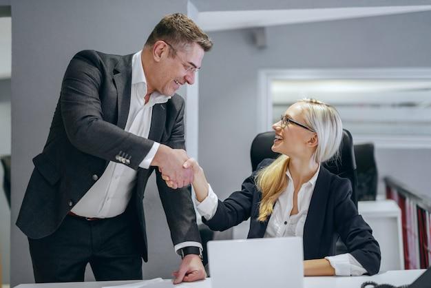 Glimlachende blonde kaukasische onderneemsterzitting in bureau en handen schudden met haar directeur. iedereen die je ontmoet, kan je iets leren.