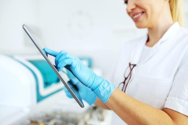 Glimlachende blonde laboratoriumassistent die met rubberhandschoenen tablet houdt en testresultaten invoert.