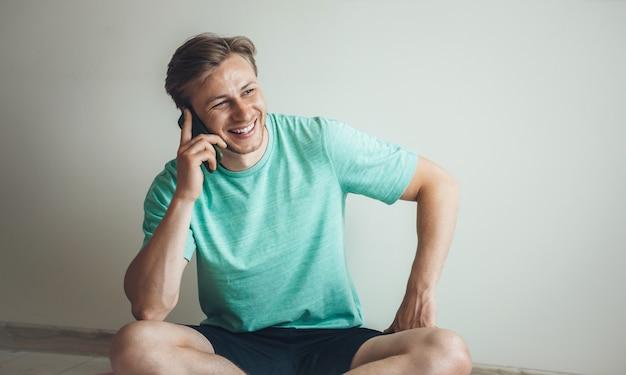 Glimlachende blonde man met een pauze tijdens de fitnessles thuis en praten over de telefoon