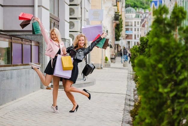 Glimlachende blonde meisjes met boodschappentassen staan