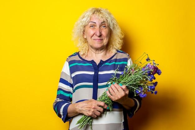 Glimlachende blonde oude vrouw in een gestreepte jurk met een boeket bloemen op een gele ondergrond