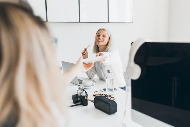 Glimlachende blonde secretaresse overhandigde documenten aan collega en koffie drinken