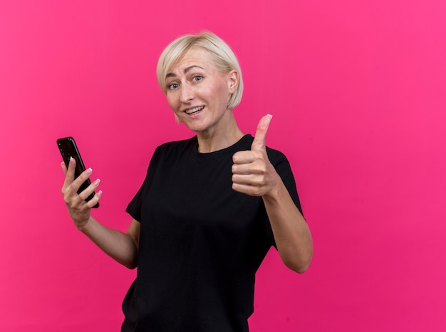 Glimlachende blonde slavische vrouw die op middelbare leeftijd mobiele telefoon houdt die duim toont die omhoog op karmozijnrode muur met exemplaarruimte wordt geïsoleerd