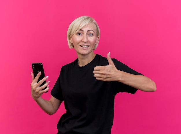 Glimlachende blonde slavische vrouw die op middelbare leeftijd mobiele telefoon houdt die voorzijde toont die duim toont die omhoog op roze muur wordt geïsoleerd