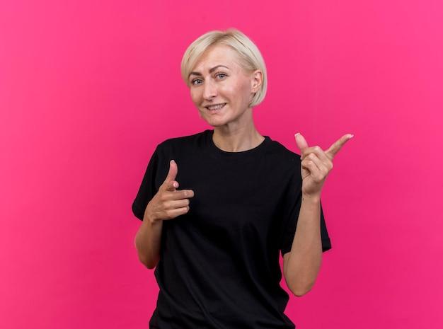Glimlachende blonde slavische vrouw die van middelbare leeftijd naar voorzijde kijkt en camera bekijkt die op roze muur met exemplaarruimte wordt geïsoleerd