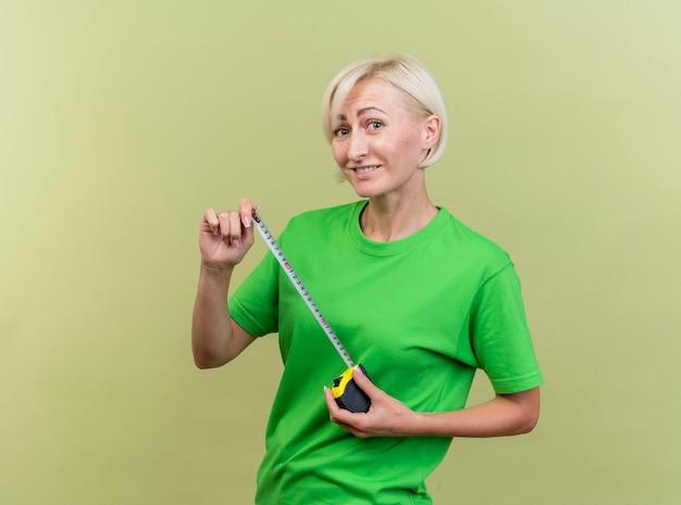 Glimlachende blonde slavische vrouw op middelbare leeftijd die de meter van de de holdingsband aan de voorzijde bekijken die op olijfgroene muur met exemplaarruimte wordt geïsoleerd