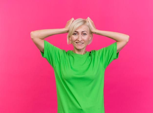 Glimlachende blonde slavische vrouw van middelbare leeftijd die camera bekijkt die handen op hoofd zet dat op karmozijnrode achtergrond wordt geïsoleerd