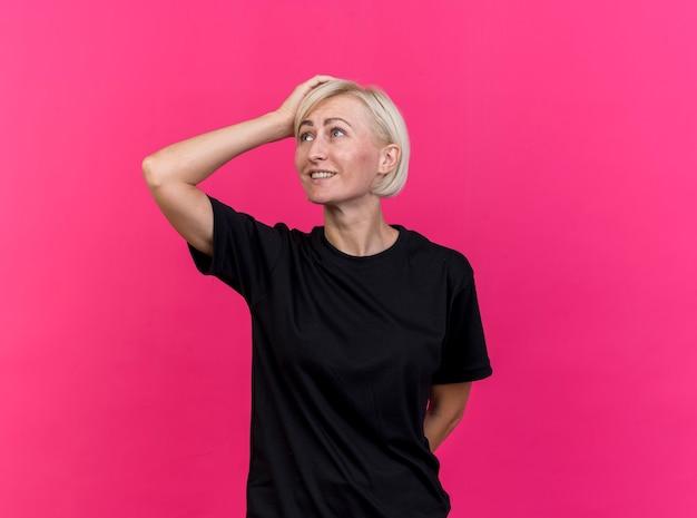 Glimlachende blonde slavische vrouw van middelbare leeftijd die de handen achter de rug en op het hoofd houdt die naar kant kijken die op karmozijnrode achtergrond met exemplaarruimte wordt geïsoleerd