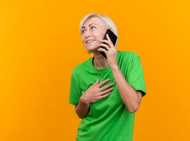 Glimlachende blonde slavische vrouw van middelbare leeftijd die op telefoon spreekt die hand op borst houdt die kant bekijkt die op gele achtergrond met exemplaarruimte wordt geïsoleerd