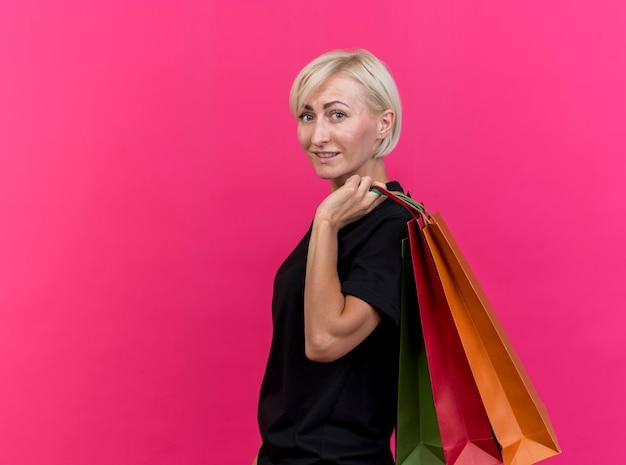 Glimlachende blonde slavische vrouw van middelbare leeftijd die zich in profielmening bevindt die het winkelen zakken op schouder houdt die op karmozijnrode muur met exemplaarruimte wordt geïsoleerd