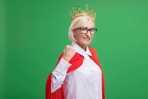 Glimlachende blonde superheld vrouw van middelbare leeftijd in rode cape met een bril en kroon
