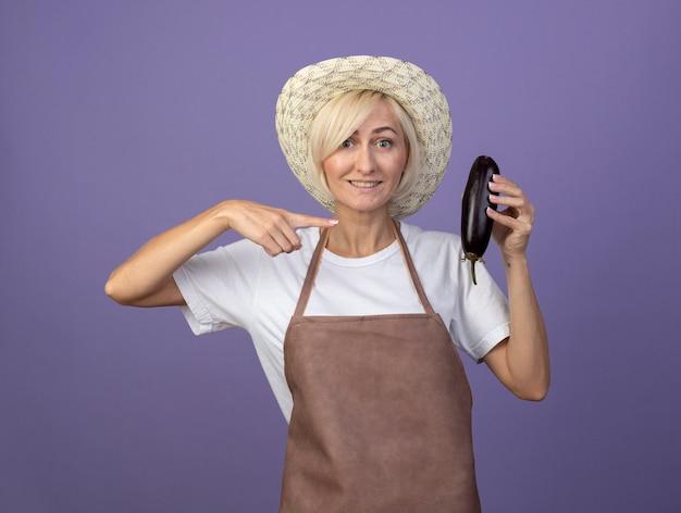 Glimlachende blonde tuinmanvrouw van middelbare leeftijd in uniform met hoed die vasthoudt en wijst naar aubergine geïsoleerd op paarse muur