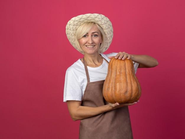 Glimlachende blonde tuinmanvrouw van middelbare leeftijd in uniform met hoed met butternut-pompoen geïsoleerd op karmozijnrode muur met kopieerruimte