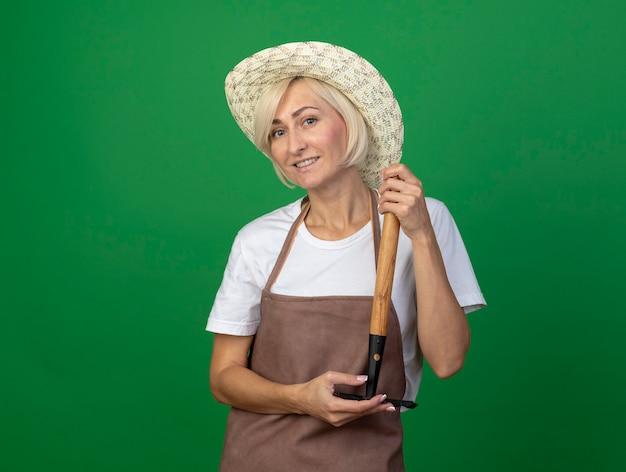 Glimlachende blonde tuinmanvrouw van middelbare leeftijd in uniform met hoed met hark ondersteboven geïsoleerd op groene muur met kopieerruimte