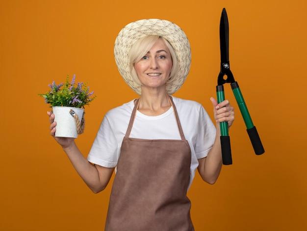 Glimlachende blonde tuinmanvrouw van middelbare leeftijd in uniform met hoed met heggenschaar en bloempot kijkend naar voorkant geïsoleerd op oranje muur